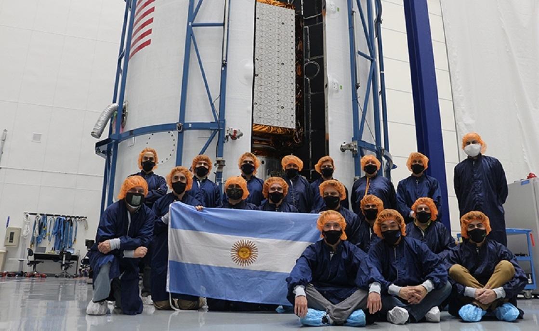 El satélite SAOCOM 1B plegado, en el interior de la cofia del lanzador Falcon 9, y el equipo de ingenieros argentinos en Cabo Cañaveral.