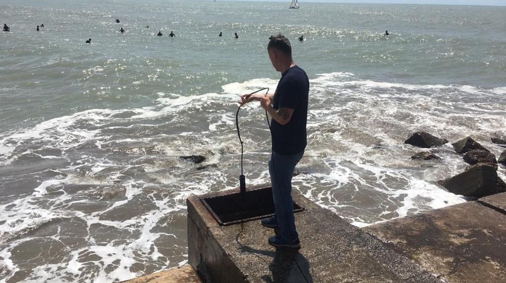 Toma de muestras de agua marina, hechas en la escollera norte de Mar del Plata.